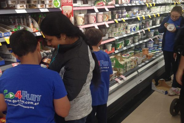 Parents and children reading nutrition labels at the supermarket. Link displays a larger version of the image.